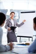 smart businesswoman standing by whiteboard and explaining her ideas - stock photo