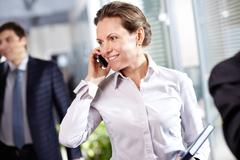 Image of modern businesswoman with cellular phone in working environment Stock Photos