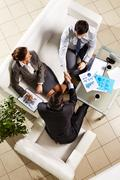 Above angle of successful associates making agreement at meeting Stock Photos