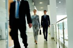 businesspeople going along corridor inside office building - stock photo