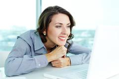 Stock Photo of smiling business woman looking at the screen of computer