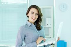 smiling business woman with laptop looking at camera - stock photo