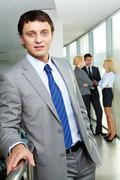 Portrait of a young confident businessman with working team on background Stock Photos