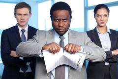 portrait of african businessman tearing contract while looking at camera with tw - stock photo