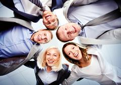 Below view of several happy business partners looking at camera while embracing Stock Photos