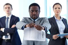 Stock Photo of portrait of african businessman tearing contract while looking at camera with tw