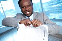 portrait of angry african businessman tearing contract and looking at camera - stock photo