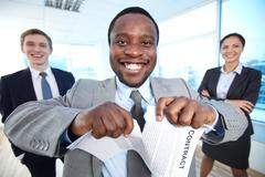 portrait of happy african businessman tearing contract while looking at camera w - stock photo