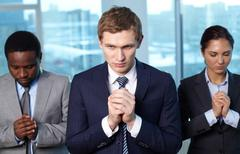 three business partners asking lord to help them - stock photo
