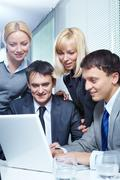 four business people working with laptop in office - stock photo