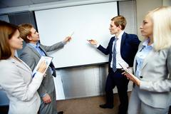 two confident businessmen pointing at whiteboard while making speech at meeting - stock photo