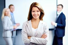 portrait of a smiling business woman looking at camera with three employees behi - stock photo