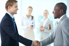 portrait of happy leaders handshaking and two females applauding on background - stock photo