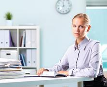 portrait of a young businesswoman at her workplace looking at camera - stock photo