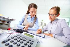 portrait of two businesswomen working with papers in office - stock photo