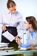 portrait of two businesswomen discussing papers in office - stock photo