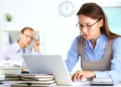 portrait of pretty secretary typing in office - stock photo