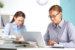portrait of pretty secretary working with laptop in office - stock photo