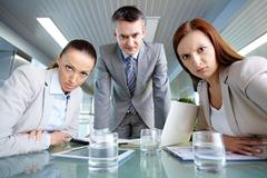Serious boss his two employees looking at camera with displeasure Stock Photos