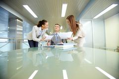 inspirated boss sitting at workplace surrounded by two secretaries - stock photo
