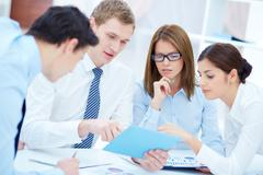 group of business partners interacting while planning work at meeting - stock photo