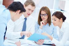 Ryhmä liikekumppaneita vuorovaikutuksessa, kun suunnittelet työtä kokouksessa Kuvituskuvat