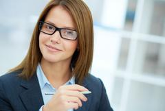 portrait of young businesswoman in eyeglasses looking at camera - stock photo
