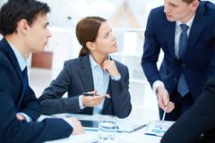 Group of business partners listening to young manager at meeting Stock Photos
