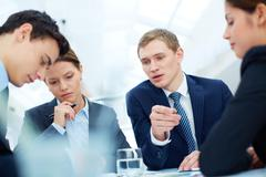 attentive business partners listening to new ideas and thinking them over at mee - stock photo