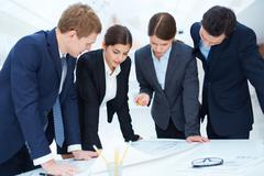 Team of engineers learning blueprint at meeting Stock Photos
