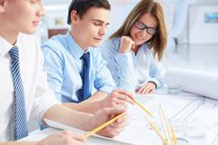 Team of engineers discussing blueprint at meeting Stock Photos