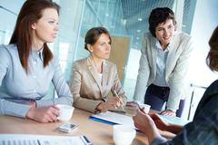 image of three attentive businesswomen listening to their employer at meeting - stock photo