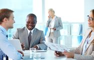 Stock Photo of portrait of confident boss smiling while his partners interacting at meeting