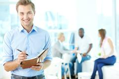 Portrait of happy man with pen and notepad looking at camera in working environm Stock Photos