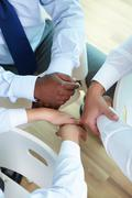 hands of three businesspeople sitting in circle - stock photo