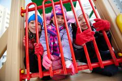 happy kids in winterwear looking at camera while having fun on playground - stock photo