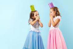Portrait of two smart girls in beautiful dresses and crowns showing their amazem Stock Photos