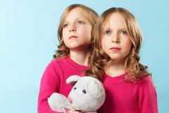 portrait of two smart girls in crimson clothes against blue background - stock photo
