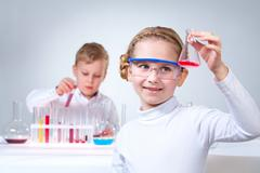 Girl in the foreground holding a flask with experimental substance, her little c Stock Photos