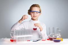 Little girl playing scientist pipetting fluid into a flask Stock Photos
