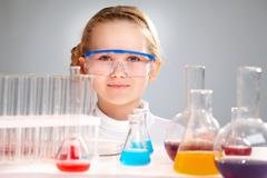 Close-up portrait of a smart-looking girl behind the table with flasks and test- Stock Photos