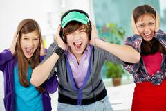 teenagers screaming and covering their ears as the sound being too loud - stock photo
