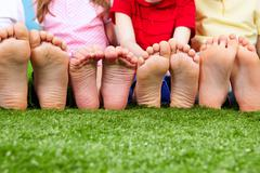 Happy friends sitting on the grass barefoot Stock Photos