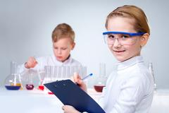 A little boy working with liquid with his assistant making notes at foreground Stock Photos