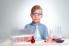 A little boy looking at camera with many flasks near by Stock Photos