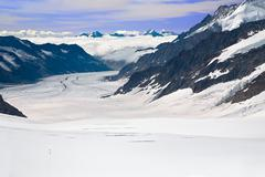 Two hikers walking towards the aletsch glacier in the alps, switzerland Stock Photos