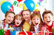 Stock Photo of group of adorable kids looking at camera at birthday party