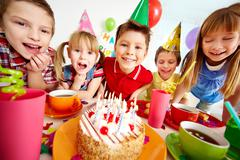 Group of adorable kids gathered around birthday cake with candles Stock Photos