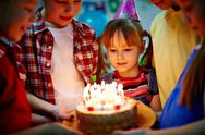 Stock Photo of group of adorable kids looking at birthday cake with candles