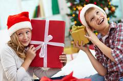 Stock Photo of portrait of happy siblings holding giftboxes and guessing what is inside on chri